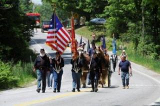 people in military uniform and horses walking down a street
