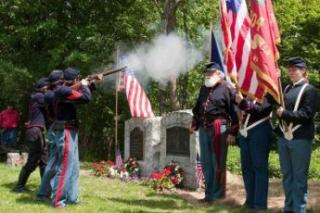 group of people in old fashioned military uniform shooting rifles at a cemetery
