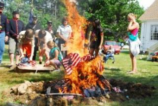 group of people burning tattered flags