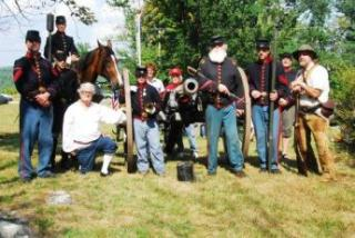 group of people in old fashioned military uniforms with a horse