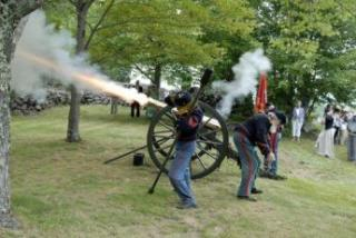 group of people in military uniform shooting a cannon